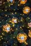 Enorm guld- jul klumpa ihop sig på en grön gran Royaltyfri Fotografi