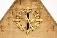 Enorm guld- klocka på fasaden av en byggnad Arkitektonisk det Arkivfoton