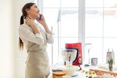 Enorm härlig matlagning i kök och samtal på telefonen fotografering för bildbyråer