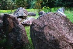 Enorm naturlig sten i parkera på gräset arkivbild