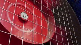Enorm roterande röd kylare fungerar intensivt bak tunn grå skyddsgaller arkivfilmer