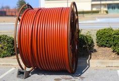 Enorm rulle av orange kabel för underjordiskt sammanträde för kabelinstallation längs en gata arkivbild