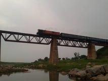 Enorm sikt av ett drev som passerar på en gammal järnbro fotografering för bildbyråer