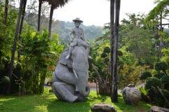 Enorm skulptur av mansammanträde på ett elefant arkivbild