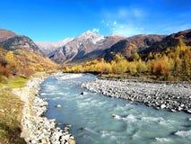 Enorm wildernislandschap in Georgië tijdens een trekking in het verre svanetigebied met een ijzige rivier en de herfstbergen stock fotografie