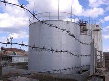 Enorma behållare för behållarebehållarebehållare för reserv- förädling för flygbränsleolja som lagras bak bevakad taggtråd arkivbilder