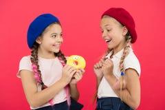 Enorma fans för ungar av bakade donuts Söt munk för aktie Flickor i baskerhattar rymmer röd bakgrund för den glasade munken Skämt arkivbilder