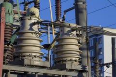 Enorma keramiska isolatorer på hög-spänning kraftledningar arkivbilder