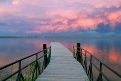 Enorma moln över en fiskepir på solnedgången Arkivfoto