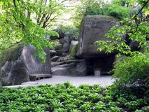 Enorma stenstenblock med dekorativa bänkar och en tabell på bakgrunden av gröna dekorativa växter Arkivfoton