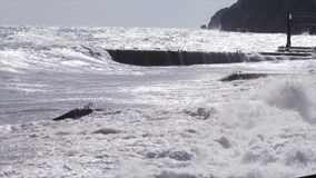 Enorma stormiga vågor som kraschar nära stadsinvallningen skjutit Stor havsvågfärgstänk Att rasa vinkar i molnigt väder lager videofilmer