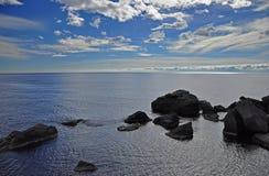 Enorma svarta stenar ligger i ett blått hav på en blå himmel med vita moln royaltyfri fotografi