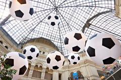 Enorma uppblåsbara fotbollbollar under kupol av supermarket Royaltyfria Bilder