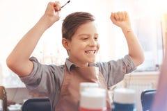 Enorme con il ragazzo di emozioni che si eccita mentre dipingendo Fotografia Stock