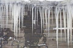 Enorme Eiszapfen hängen vom Dach des alten Hauses Stockbild