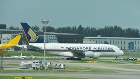 Enorme estupendo de Singapore Airlines Airbus 380 que es remolcado a través de pista de rodaje Fotografía de archivo