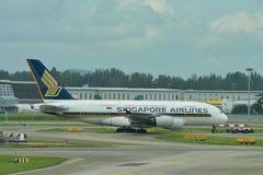 Enorme estupendo de Singapore Airlines Airbus 380 que es remolcado a través de pista de rodaje en el aeropuerto de Changi Fotos de archivo libres de regalías