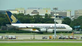 Enorme estupendo de Singapore Airlines Airbus 380 que es remolcado a través de pista de rodaje en el aeropuerto de Changi Imagen de archivo libre de regalías