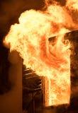 Enorme Flamme, die Haus auf Feuer ablenkt Mann, der Feuerlöscher überprüft Lizenzfreies Stockbild