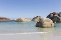 Enorme Flusssteine, die auf weißem Sand auf dem Strand stillstehen Lizenzfreies Stockbild