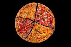 Enorme internationale Pizza auf schwarzem Hintergrund Chef gießt Olivenöl über frischem Salat in der Gaststätteküche Lizenzfreie Stockbilder