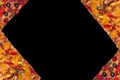 Enorme internationale Pizza auf schwarzem Hintergrund Chef gießt Olivenöl über frischem Salat in der Gaststätteküche Stockfotografie