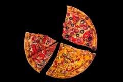 Enorme internationale Pizza auf schwarzem Hintergrund Chef gießt Olivenöl über frischem Salat in der Gaststätteküche Stockbilder