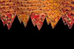 Enorme internationale Pizza auf schwarzem Hintergrund Chef gießt Olivenöl über frischem Salat in der Gaststätteküche Lizenzfreie Stockfotos