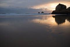Enorme Klippen der drastischen Küste, die im goldenen Sonnenuntergang auf atlantischer Küstenlinie sich reflektieren Stockfoto