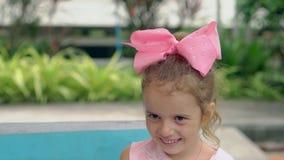 Enorme niño con el arco púrpura en las sonrisas principales contra piscina almacen de metraje de vídeo