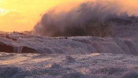 Enorme Ozeanbrandung, die über Felsen bei Sonnenuntergang zusammenstößt stockbilder