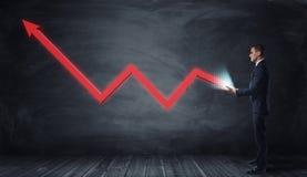 Enorme rote Linie Diagramm mit einem umgedrehten Pfeil, der von den Händen eines Geschäftsmannes wächst Stockfotografie