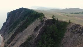 Enorme Sandstein-Gebirgsklippe mit grünen Kiefern im Baikalsee Sibirien Russland, das Luftmeerblickansicht des brummens 4k überra stock video footage