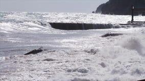 Enorme stürmische Wellen, die nahe dem Stadtdamm zusammenstoßen schuß Großes Seewellenspritzen Das Rasen bewegt in wolkiges Wette stock video footage