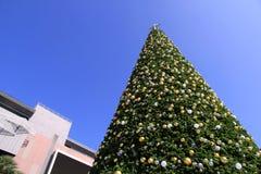 Enorme Weihnachtsbaumdekorationen und Hintergrund des blauen Himmels Stockfotos