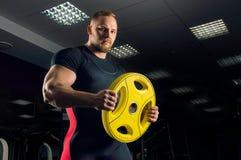 Enormer Athlet hält eine Diskette für die Stange stockbild