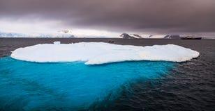 Enormer Eisberg mit blauem uderwater Teil und des Kreuzschiffs Rückseite herein Lizenzfreies Stockbild