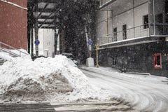 Enormer Haufen des schmutzigen Schnees und des Eises auf einer Stadtstraße Stockfotografie