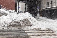 Enormer Haufen des schmutzigen Schnees und des Eises auf einer Stadtstraße Lizenzfreies Stockfoto