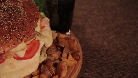 Enormer köstlicher Burger mit Kartoffeln und sprudelndem Getränk stock footage
