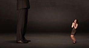 Enormer Mann mit der kleinen Geschäftsfrau, die am vorderen Konzept steht Lizenzfreies Stockbild
