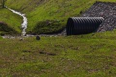 Enormer schwarzer Plastikabwasserkanal und kleiner Strom Lizenzfreie Stockfotos