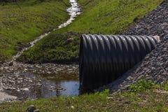 Enormer schwarzer Plastikabwasserkanal und kleiner Strom Lizenzfreies Stockbild