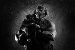 Enormer Soldat hält einen kleinen Welpen in seinen Armen Lizenzfreies Stockbild