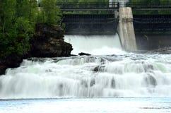 Enormer weißer Wasserfall schaukelt unten, während Wasserkraftkraftwerk Betonschranke öffnet Stockfotos
