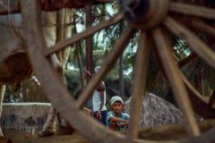 Enormes altes hölzernes Wagenrad der Weinlese-photo-1983 und Landwirtjunge stockbilder
