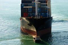 Enormes Behälterboot im Hafen mit Liegeplatzservice in der Front Großes Frachtschiff folgt Liegeplatzservice im kleinen Schiff Fr Lizenzfreies Stockfoto