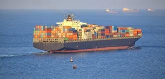 Enormes BehälterFrachtschiff abgehend vom Hafen Lizenzfreie Stockfotos