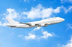 Enormes Flugzeug im Blau mit heftigen weißen Wolken lizenzfreies stockfoto