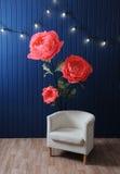 Enormes Wachstumsrosa blüht im Innenraum mit weißem Stuhl auf dem Hintergrund der blauen Wand mit Retro- Girlande Lizenzfreie Stockfotos